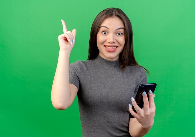 Sorridente giovane donna graziosa tenendo il telefono cellulare e alzando il dito