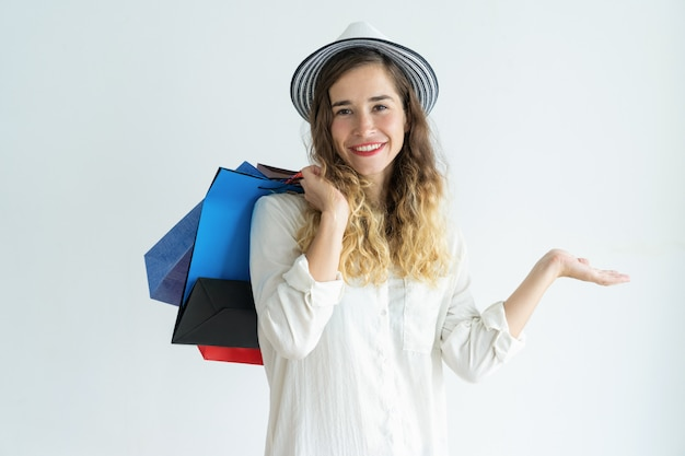 Smiling young pretty woman holding shopping bags, wearing hat