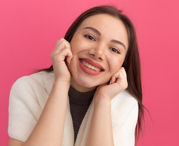 Sorridente giovane donna graziosa che tiene le mani sulle guance isolate sul muro rosa
