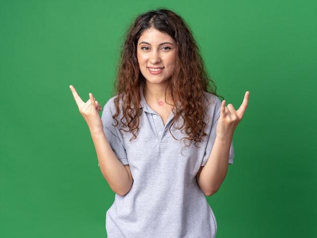 Улыбающаяся молодая красивая женщина, смотрящая на фронт, делает рок-знак изолирована на зеленой стене