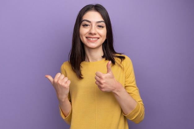 Улыбающаяся молодая красивая женщина, смотрящая на фронт, указывающая на сторону, показывающая большой палец вверх изолирована на фиолетовой стене с копией пространства