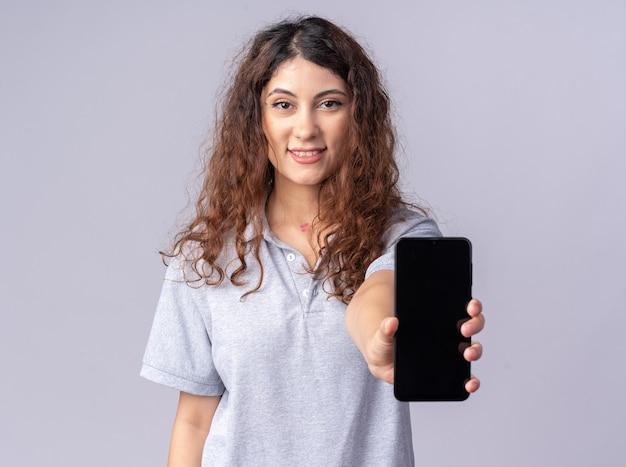 Улыбающаяся молодая красивая женщина, смотрящая на фронт, протягивая мобильный телефон к фронту, изолированному на белой стене