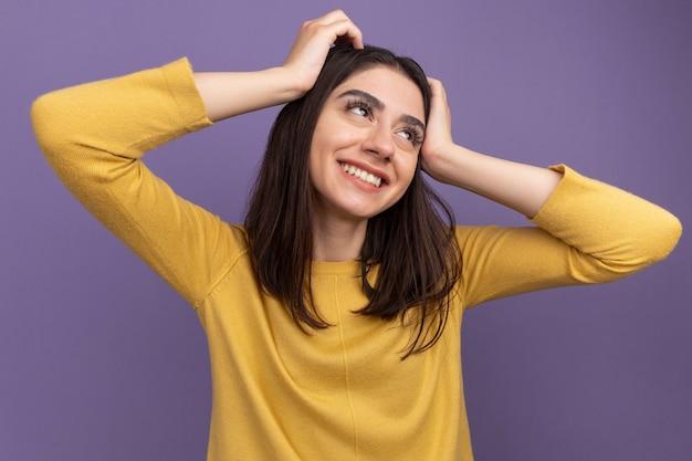 Sorridente giovane bella donna che guarda di lato mettendo le mani sulla testa isolata sul muro viola