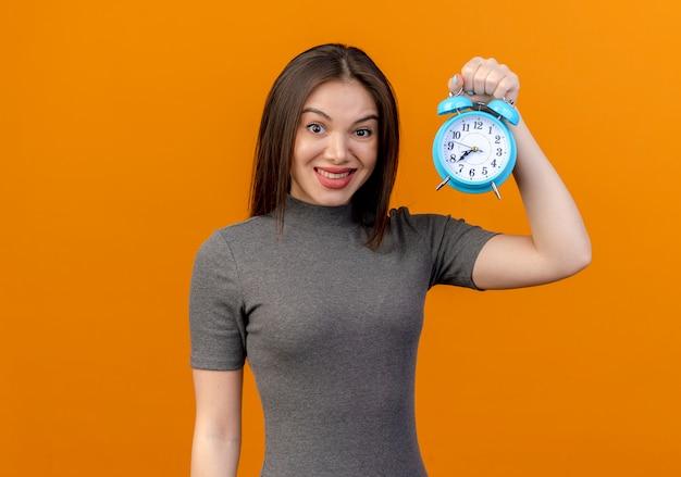 Giovane donna graziosa sorridente che alza sveglia isolata su fondo arancio con lo spazio della copia