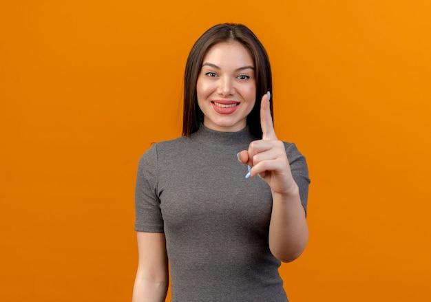 복사 공간 오렌지 배경에 고립 된 카메라에 손가락을 올리는 젊은 예쁜 여자 미소