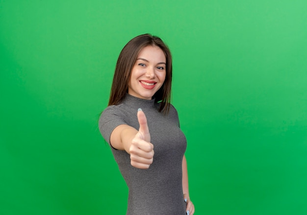 복사 공간이 녹색 배경에 고립 엄지 손가락을 보여주는 젊은 예쁜 여자 미소