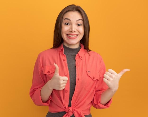 Sorridente giovane donna graziosa che mostra i pollici in su isolato sulla parete arancione