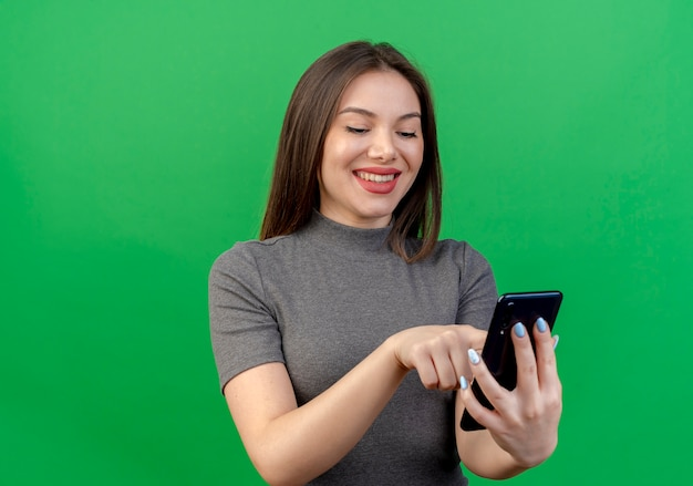 コピースペースと緑の背景に分離された携帯電話を使用して笑顔の若いきれいな女性