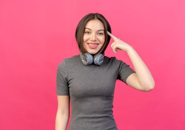 Sorridente giovane donna graziosa che indossa le cuffie sul collo mettendo il dito sul tempio isolato su sfondo rosa con copia spazio