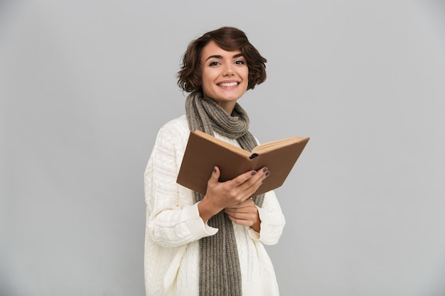 Smiling young pretty woman wearing scarf reading book.