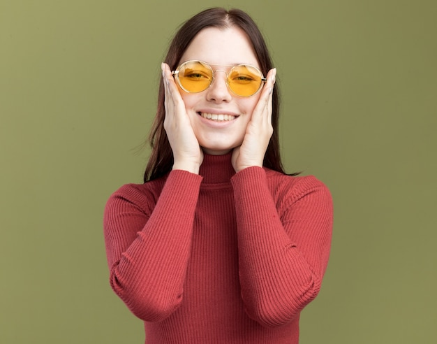 Sorridente giovane bella donna che indossa occhiali da sole tenendo le mani sul viso guardando la parte anteriore isolata sul muro verde oliva