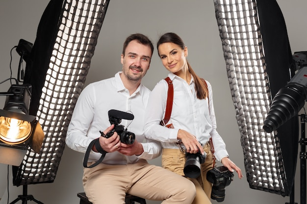 Smiling young professional photographers posing in the studio