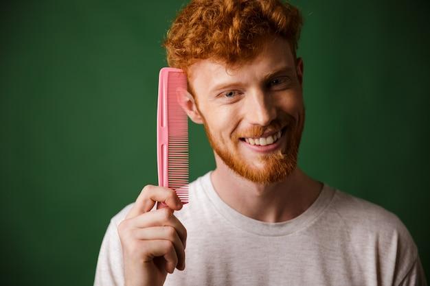 Uomo barbuto sorridente del giovane readhead che mostra pettine rosa