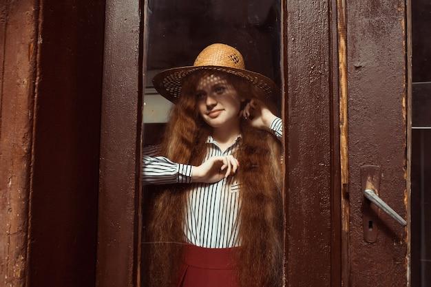 彼女の顔とそばかすに影と麦わら帽子で笑顔の若い赤い髪のモデル