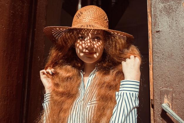 彼女の顔に影と麦わら帽子で笑顔の若い赤い髪のモデル