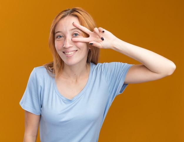 Улыбающаяся рыжая рыжая девушка с веснушками жестикулирует знак победы, глядя в камеру сквозь пальцы на оранжевом