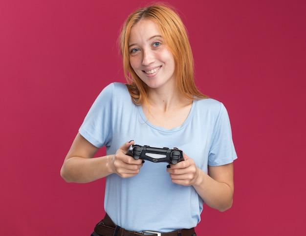 Улыбающаяся рыжая рыжая девушка с веснушками держит игровой контроллер на розовом