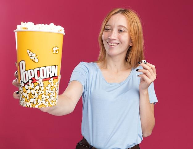 Sorridente giovane ragazza rossa allo zenzero con lentiggini che tiene e guarda il secchio di popcorn
