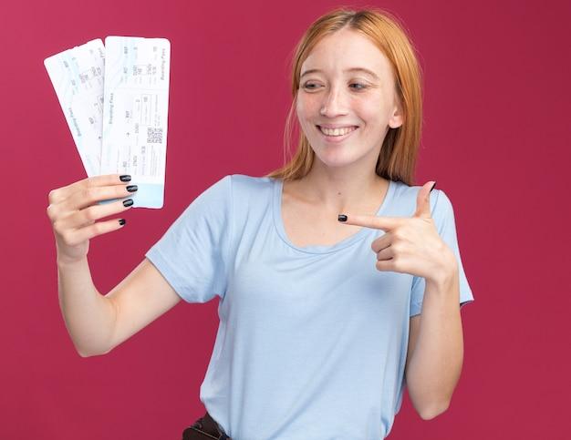 Sorridente giovane ragazza rossa allo zenzero con le lentiggini che tengono e puntano ai biglietti aerei