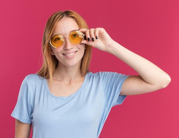 La giovane ragazza sorridente dello zenzero della testarossa con le lentiggini esamina la macchina fotografica attraverso gli occhiali da sole