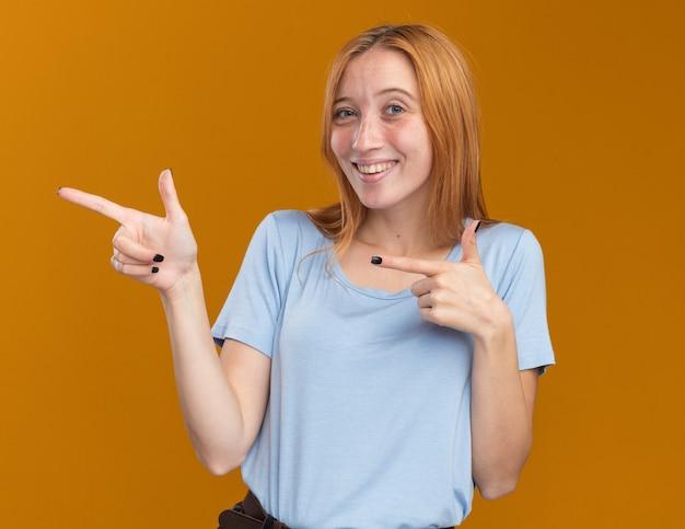 Giovane ragazza sorridente dello zenzero della testarossa con le lentiggini che indicano al lato isolato sulla parete arancio con lo spazio della copia