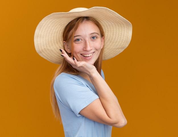 Улыбающаяся рыжая рыжая девушка с веснушками в пляжной шляпе стоит боком, положив руку на подбородок на оранжевом