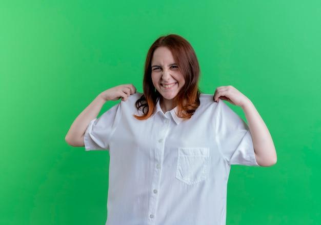 녹색에 고립 된 t- 셔츠를 잡고 웃는 젊은 빨강 머리 소녀