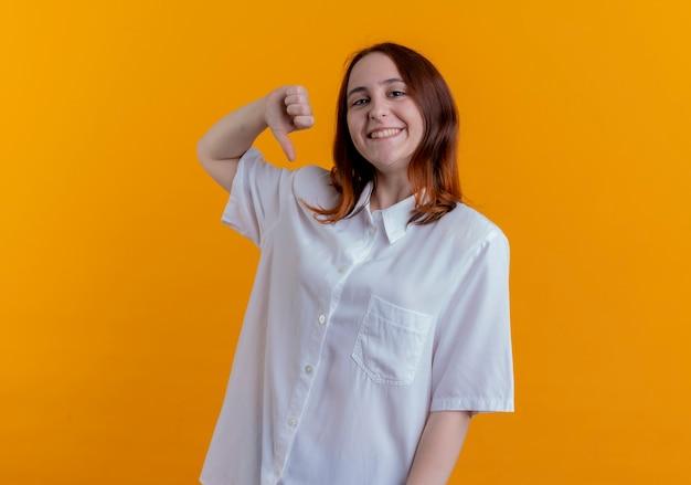 Sorridente ragazza giovane rossa il suo pollice verso il basso isolato su sfondo giallo
