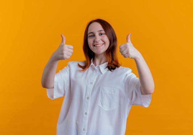 웃는 젊은 빨강 머리 소녀 그녀의 엄지 손가락에 고립 된 노란색 벽