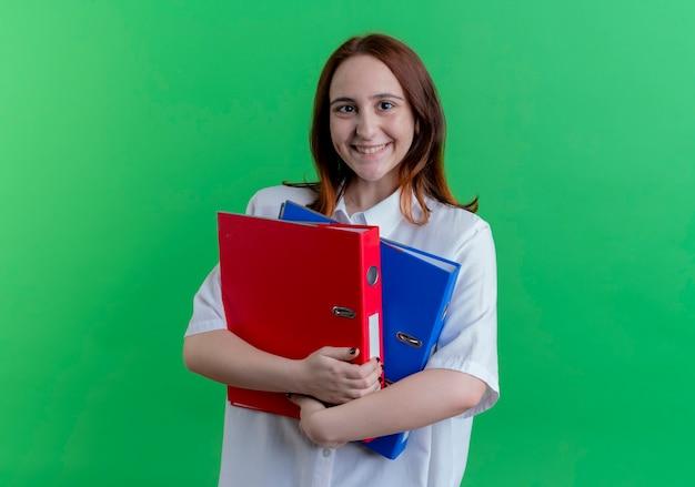 緑に分離されたフォルダーを保持している若い赤毛の女の子の笑顔
