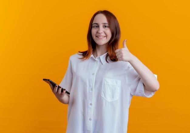 電話と彼女の親指を黄色の壁に分離して保持している若い赤毛の女の子の笑顔
