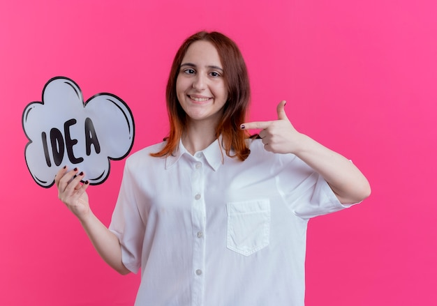 Sorridente giovane ragazza redhead holding e punti alla bolla idea isolata sul rosa