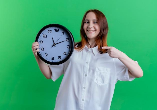 Sorridente giovane ragazza redhead holding e punti all'orologio da parete isolato su verde