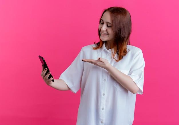 Sorridente giovane ragazza redhead holding e punti con la mano al telefono isolato sul rosa