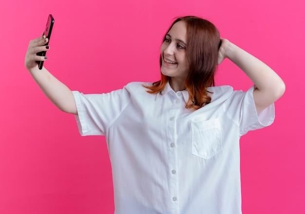 Sorridente ragazza giovane rossa prendere un selfie e mettere la mano dietro la testa isolata sul rosa