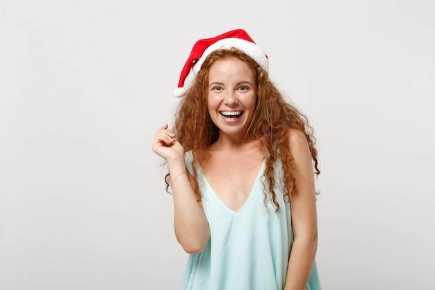 明るい服、白い背景で隔離のクリスマス帽子、スタジオの肖像画で若い赤毛サンタの女の子を笑顔。明けましておめでとうございます2020年のお祝いの休日のコンセプト。コピースペースをモックアップします。探しているカメラ。