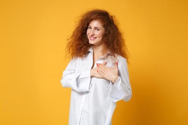 Sorridente giovane donna dai capelli rossi in camicia bianca casual in posa isolata sul muro giallo arancione