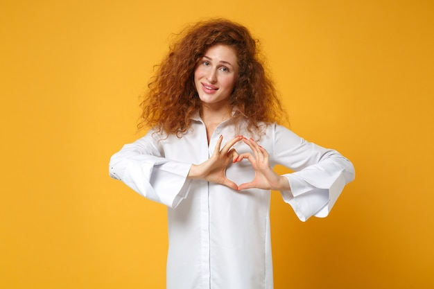 Улыбающаяся молодая рыжая девушка в повседневной белой рубашке позирует изолированной на желто-оранжевой стене