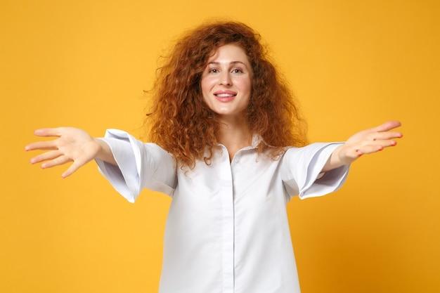 노란색 오렌지 벽에 고립 된 캐주얼 흰색 셔츠 포즈에 웃는 젊은 빨간 머리 여자 소녀 무료 사진