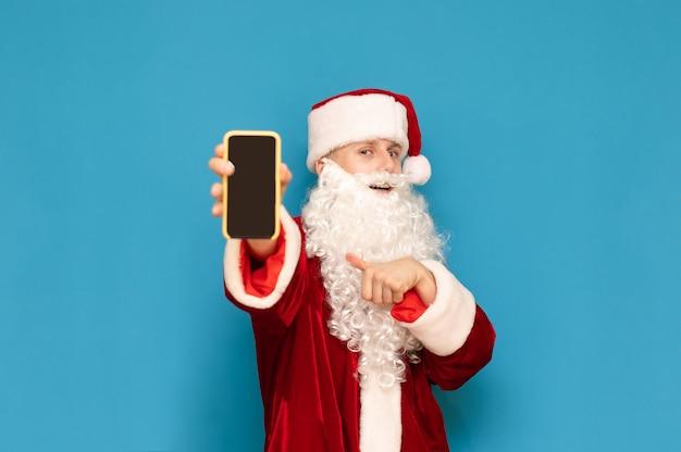 青に手でスマートフォンで若いサンタクロースを笑顔、カメラに黒い画面で電話を示し、指を示しています