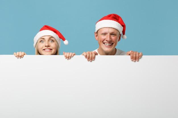 クリスマスの帽子で若いサンタカップルの友人の男と女の笑顔