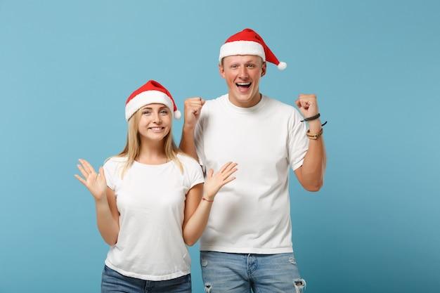 Sorridente giovane coppia di amici di babbo natale ragazzo e donna in posa del cappello di natale