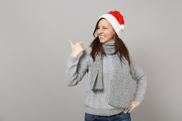 Smiling young santa girl in gray sweater, scarf christmas hat looking, pointing thumb aside isolated on grey wall background. happy new year 2019 celebration holiday party concept. mock up copy space.