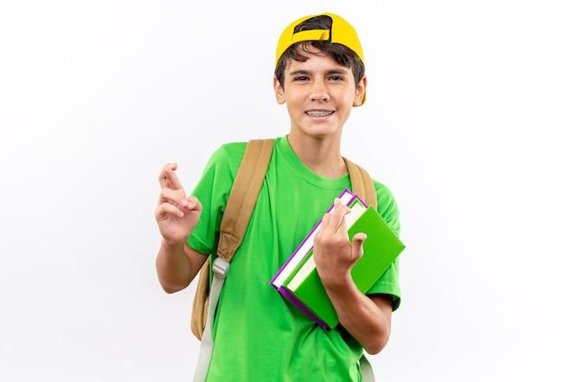 白い壁に隔離された指を交差させる本を保持しているキャップとバックパックを身に着けている若い男子生徒の笑顔