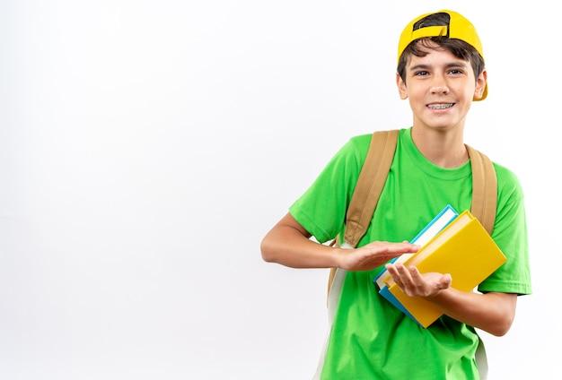 Sorridente giovane scolaro che indossa uno zaino con cappuccio che tiene libri isolati sul muro bianco con spazio per la copia