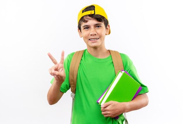 白い壁に隔離された平和のジェスチャーを示す本を保持しているキャップとバックパックを身に着けている若い男子生徒の笑顔