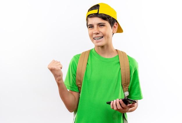 흰 벽에 격리된 예 제스처를 보여주는 전화를 들고 모자를 쓰고 배낭을 메고 웃고 있는 어린 학교 소년