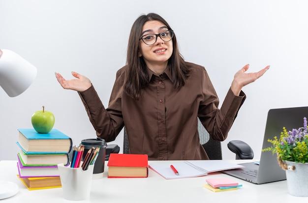 眼鏡をかけている笑顔の若い女子高生は、手を広げて学校のツールとテーブルに座っています