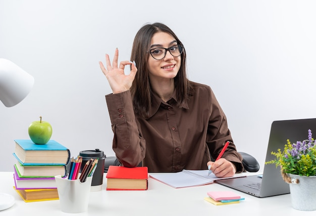 Smiling young school woman wearing glasses sits at table with school tools showing okay gesture