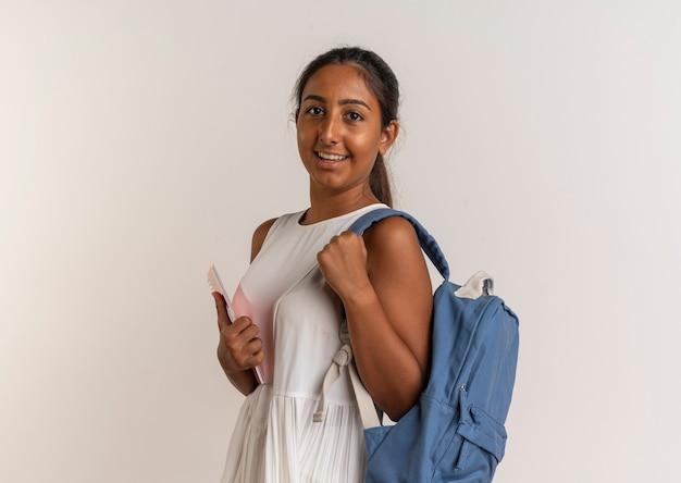 Улыбающаяся молодая школьница в задней сумке, держащая ноутбук на белом